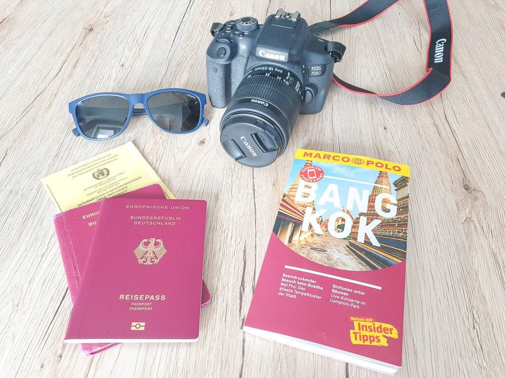 Tisch mit Kamera, Sonnenbrille, Reisepässen, Impfpass und Reiseführer - Bangkok - Reisevorbereitungen