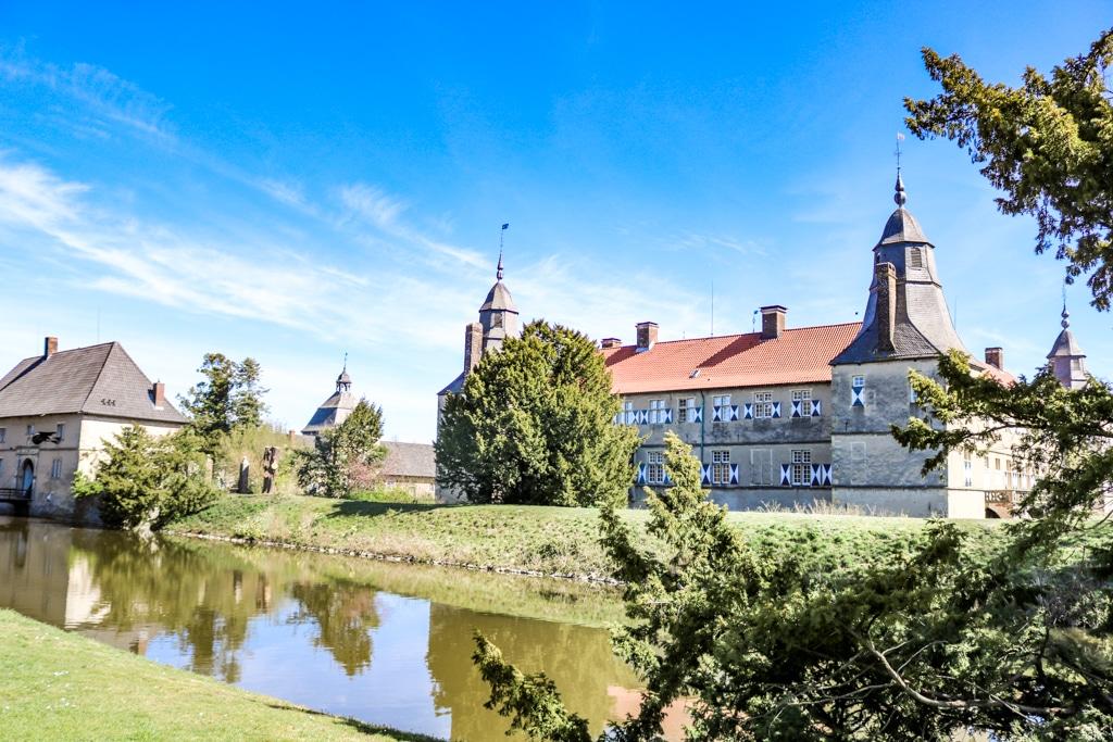 Schloss Westerwinkel in Ascheberg - Blick auf ein Schloss mit karierten Fensterläden über einen Wassergraben hinweg