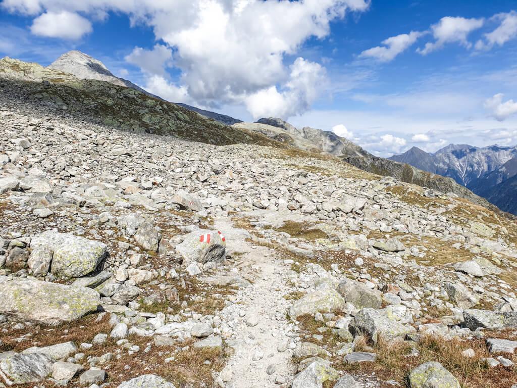 schmaler Weg mit weiß-roter Markierung für den Wanderweg führt zwischen Geröllfeldern über einen Bergkamm. Im Hintergrund sind hohe Berge bei blauem Himmel zu sehen