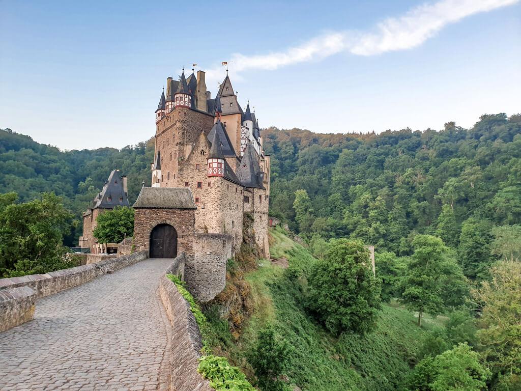 Burg Eltz im Morgenlicht inmitten von grünen Bäumen