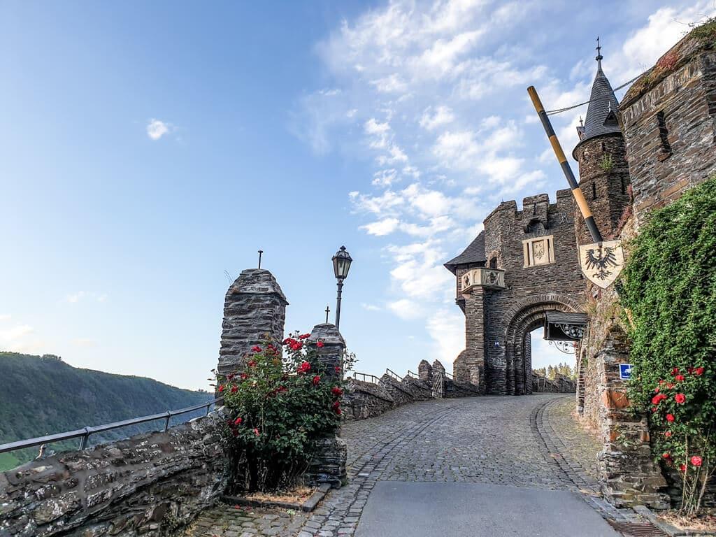 Eingangstor zur Reichsburg Cochem mit goldenem Wappen und geöffneter Schranke