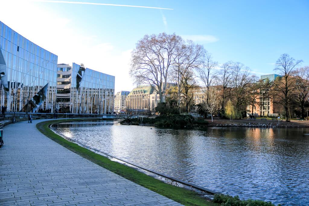 Teich auf der rechten Seite - links ein Gehweg und verglaste Gebäude