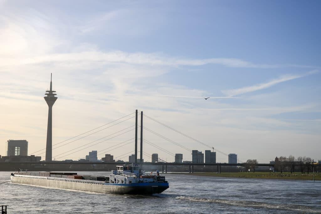 Boot fährt auf dem Rhein - dahinter eine Brücke und der Fernsehturm