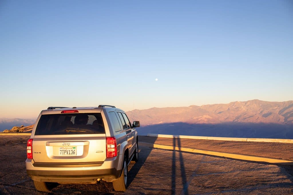 Auto an einem Aussichtspunkt bei Sonnenaufgang
