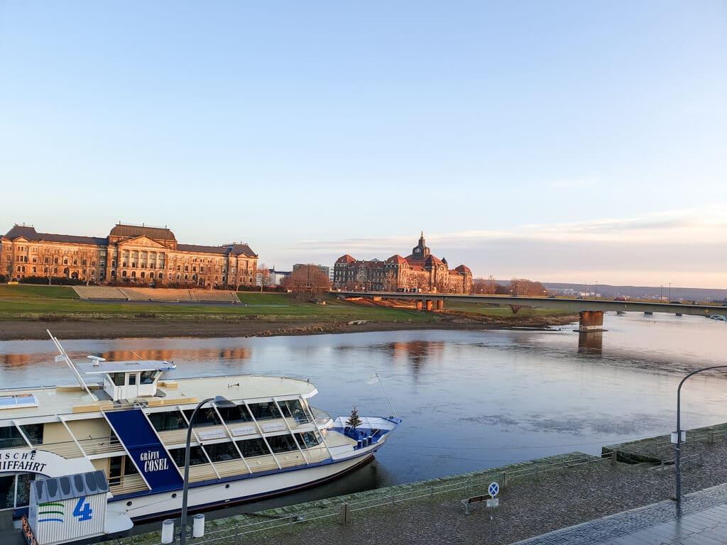 Dresden: Blick von der Brühlschen Terrasse über die Elbe am Morgen - links historische Gebäude, im Vordergrund eine Fähre