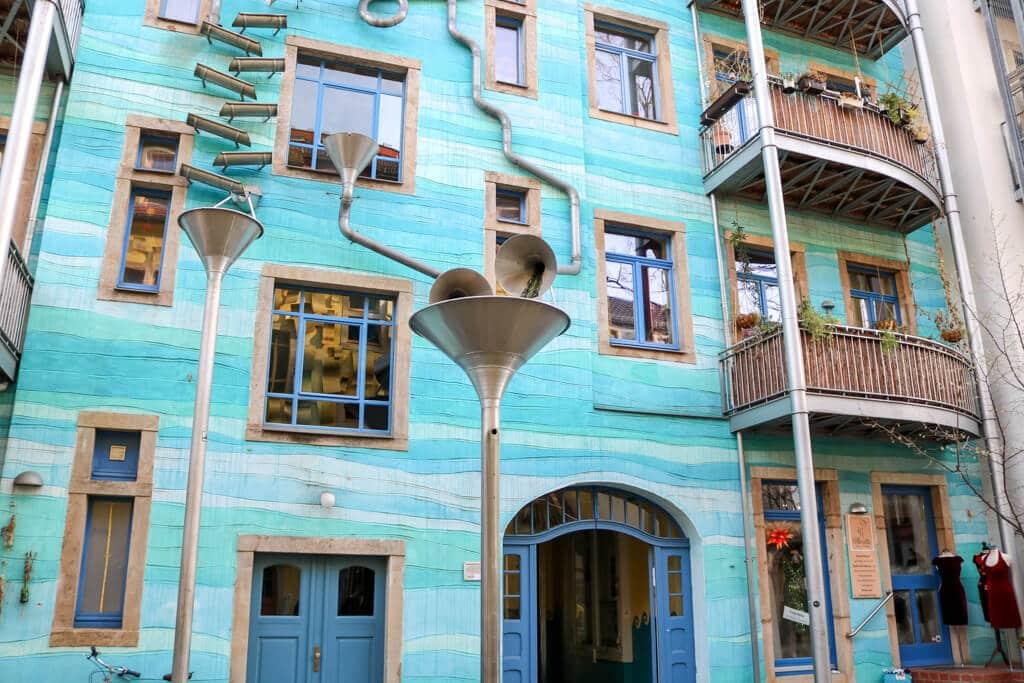 türkis angemalte Hauswand mit silbernen Fallrohren als Kunstobjekte