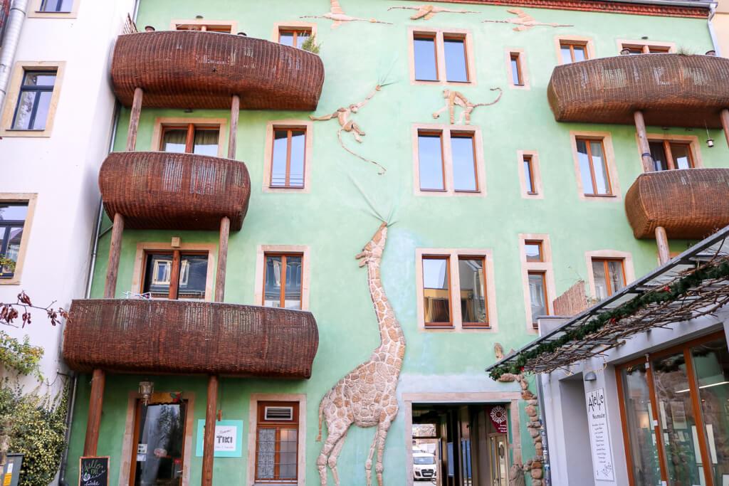 grüne Hauswand mit aufgemalter Giraffe und Affen