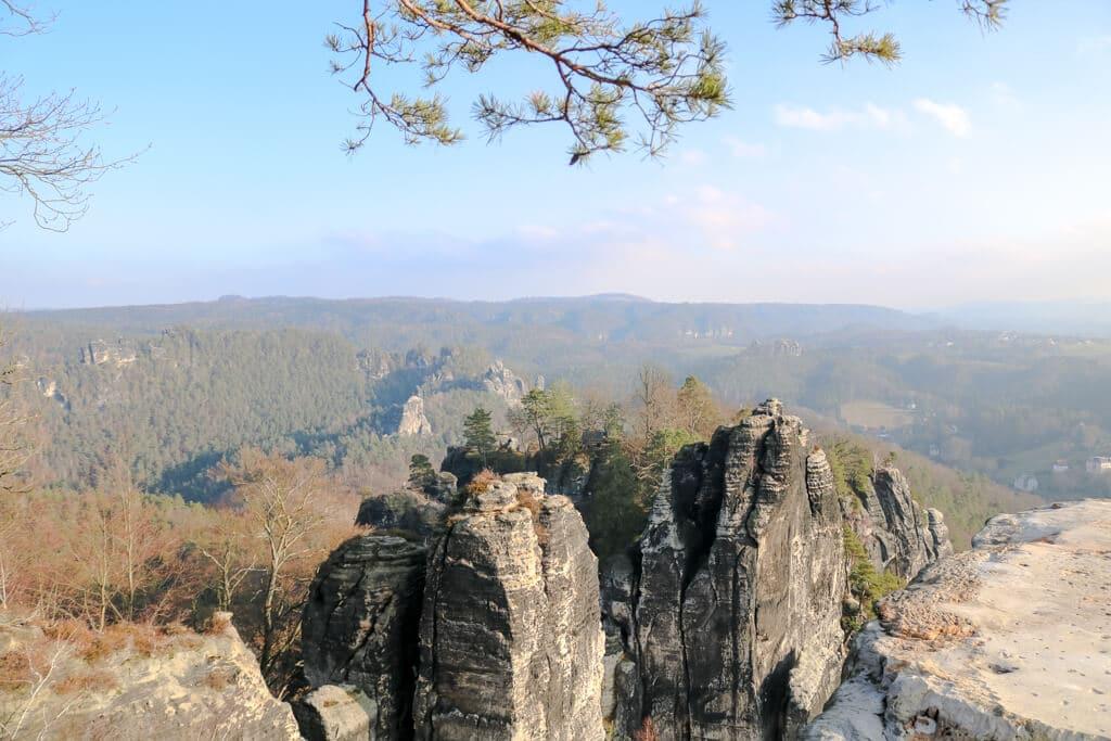 Felsen im Vordergrund, dahinter ein grünes Tal mit blauem Himmel