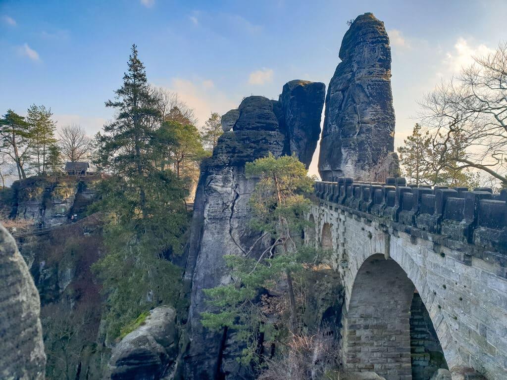 Steinbrücke mit Rundbögen inmitten von Felsen und Bäumen
