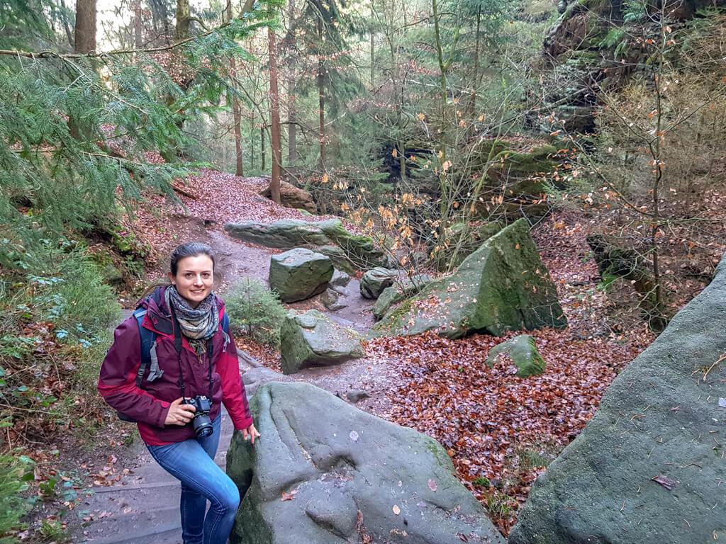 Frau steht auf steinigem Wanderweg im Wald
