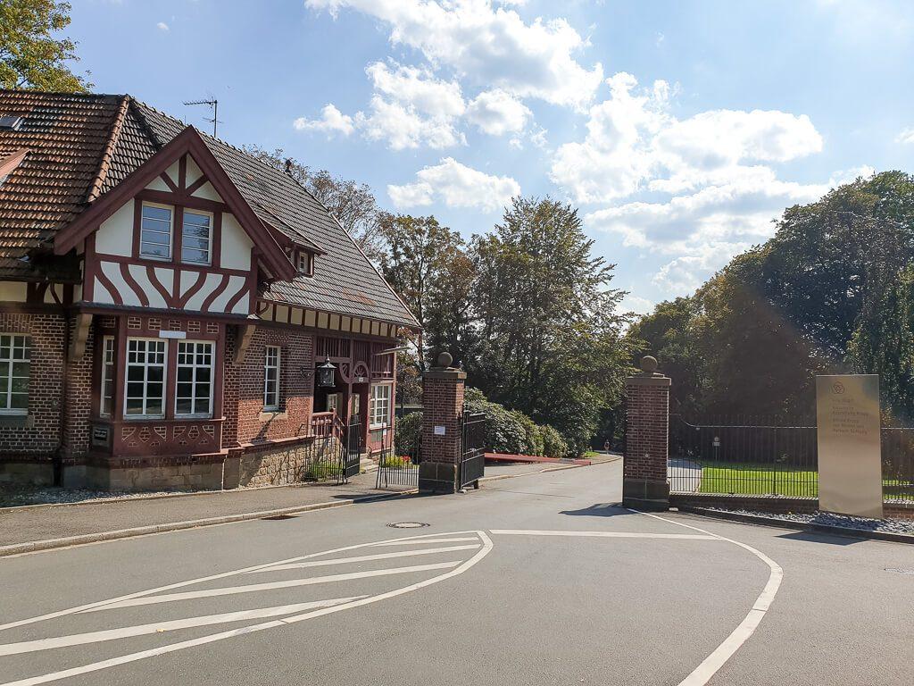Villa Hügel Essen: Straße führt zu Eingangstor mit Fachwerkhaus aus Klinker