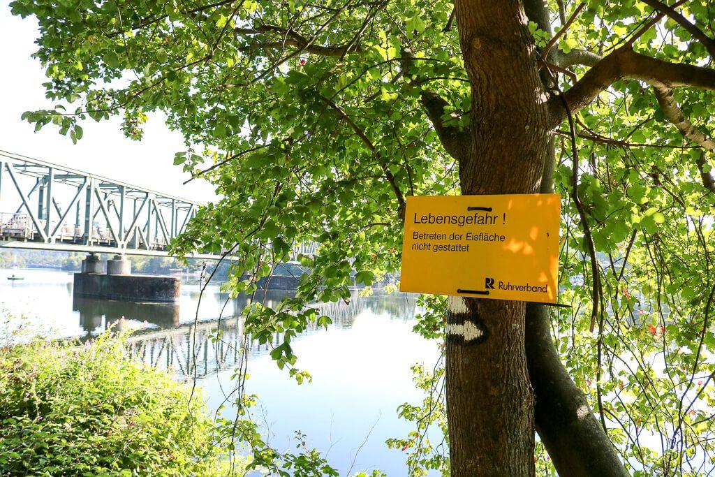 gelbes Hinweisschild an einem Baum - im Hintergrund eine Brücke und ein See