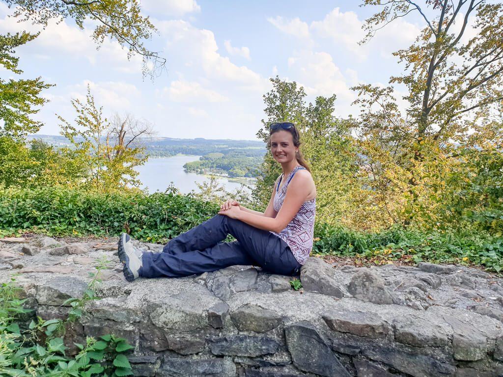 Ruine Neu-Isenburg am Baldeneysee: Frau sitzt auf Mauer - dahinter Wald und ein See