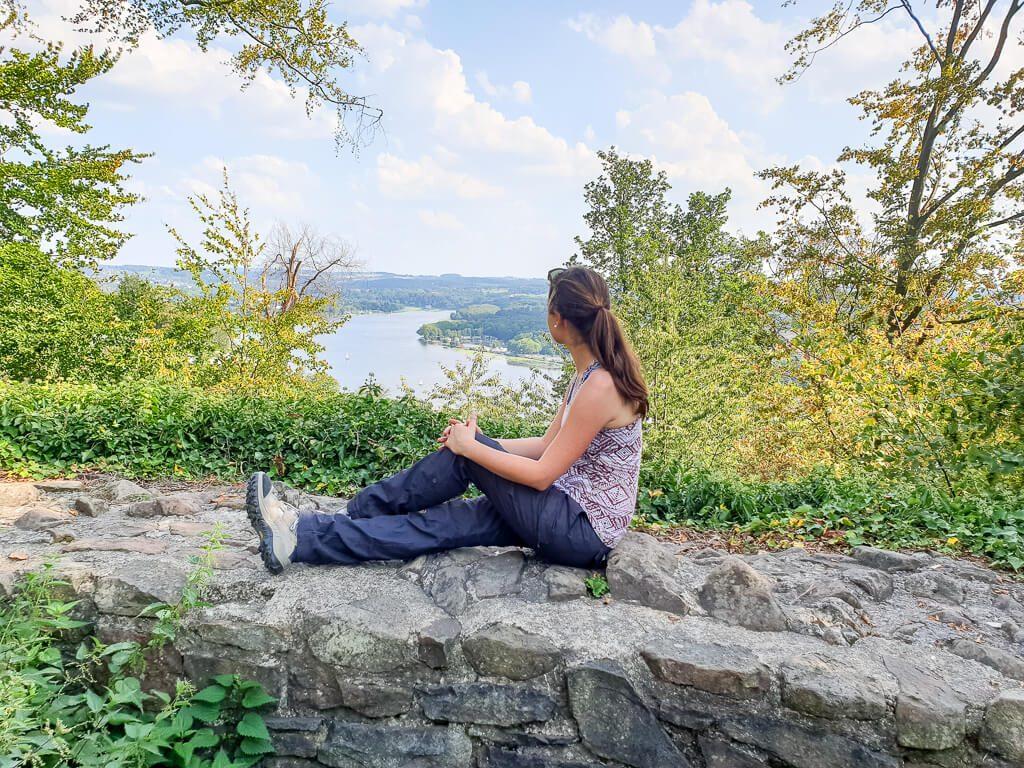 Frau sitzt auf Mauer und Blickt auf den dahinter liegenden See