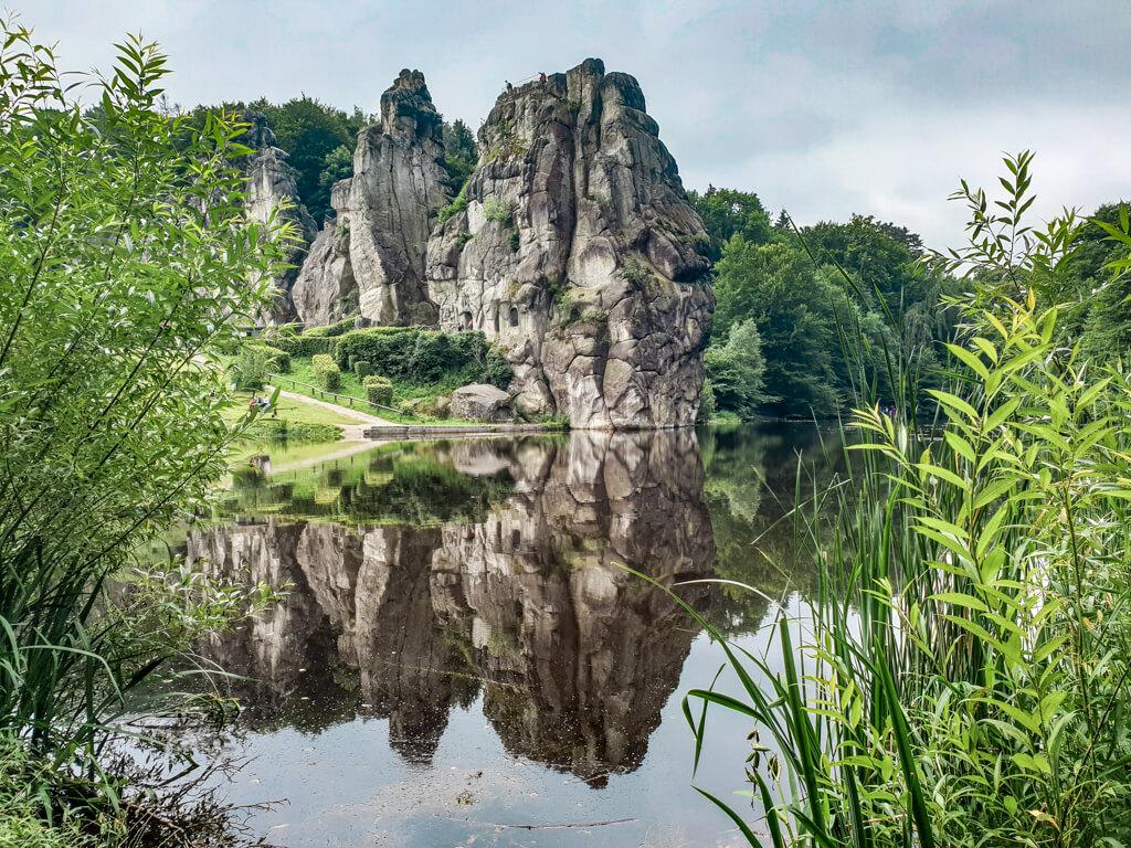 Externsteine spiegeln sich im darunter liegenden See. Im Vordergrund sind einige Gräser sichtbar