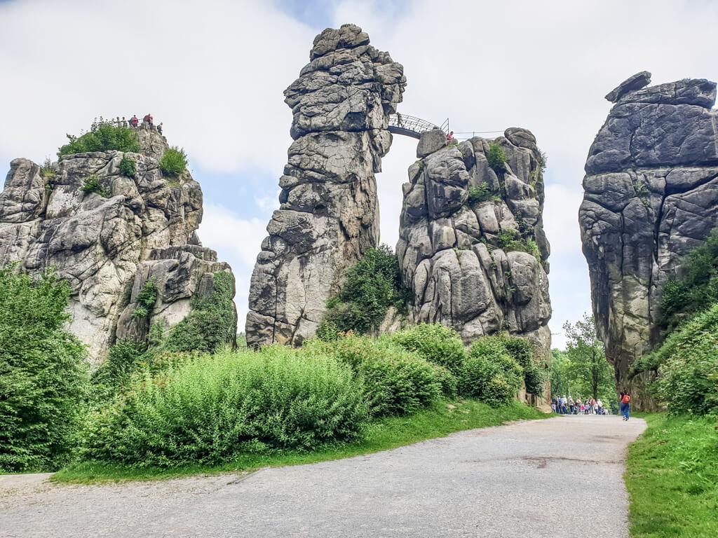 Weg führt zwischen zwei Felsen der Externsteine hindurch. Alle vier Felsen sind in einer Reihe sichtbar