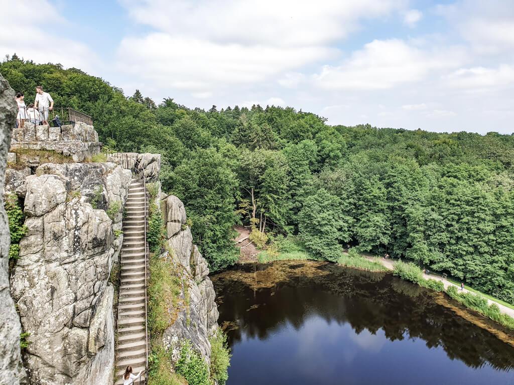 Blick von einem Fels der Externsteine hinüber auf einen anderen sowie den darunter liegenden See mit Spiegelung des Waldes