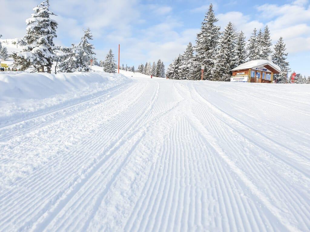 frisch präparierte Piste mit Blick auf eine kleine Holzhütte im Schnee