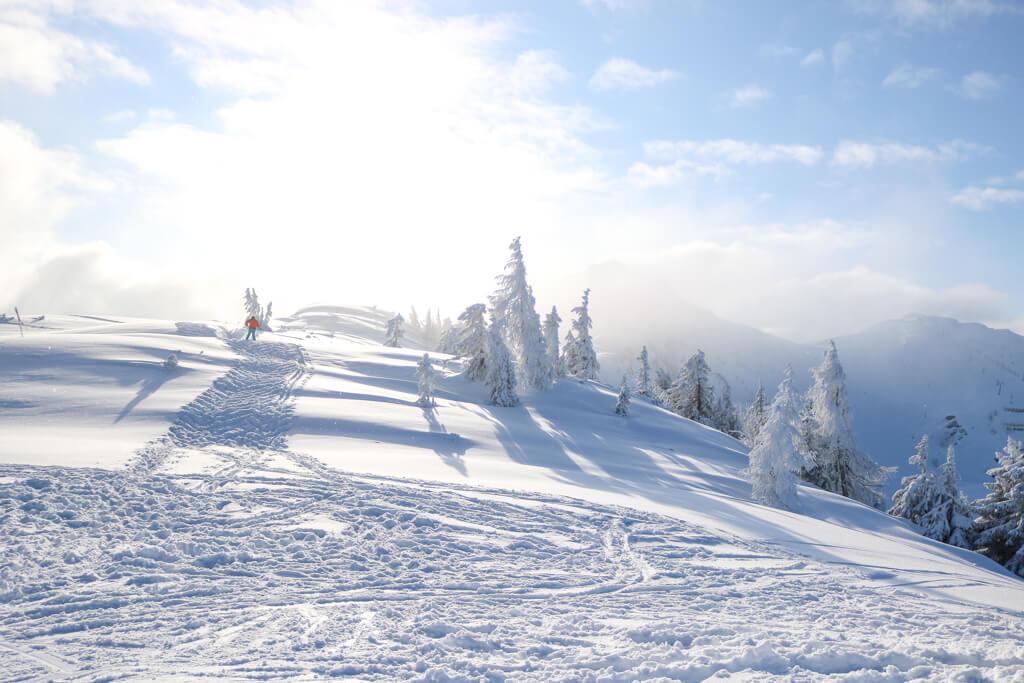 Blick auf strahlenden Sonnenschein und verschneite Berge