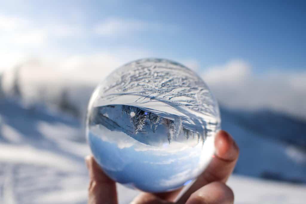 Glaskugel in der sich eine Schneelandschaft spiegelt
