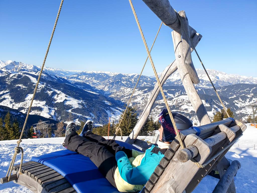 Frau sitzt auf Hängesesseln in den Bergen