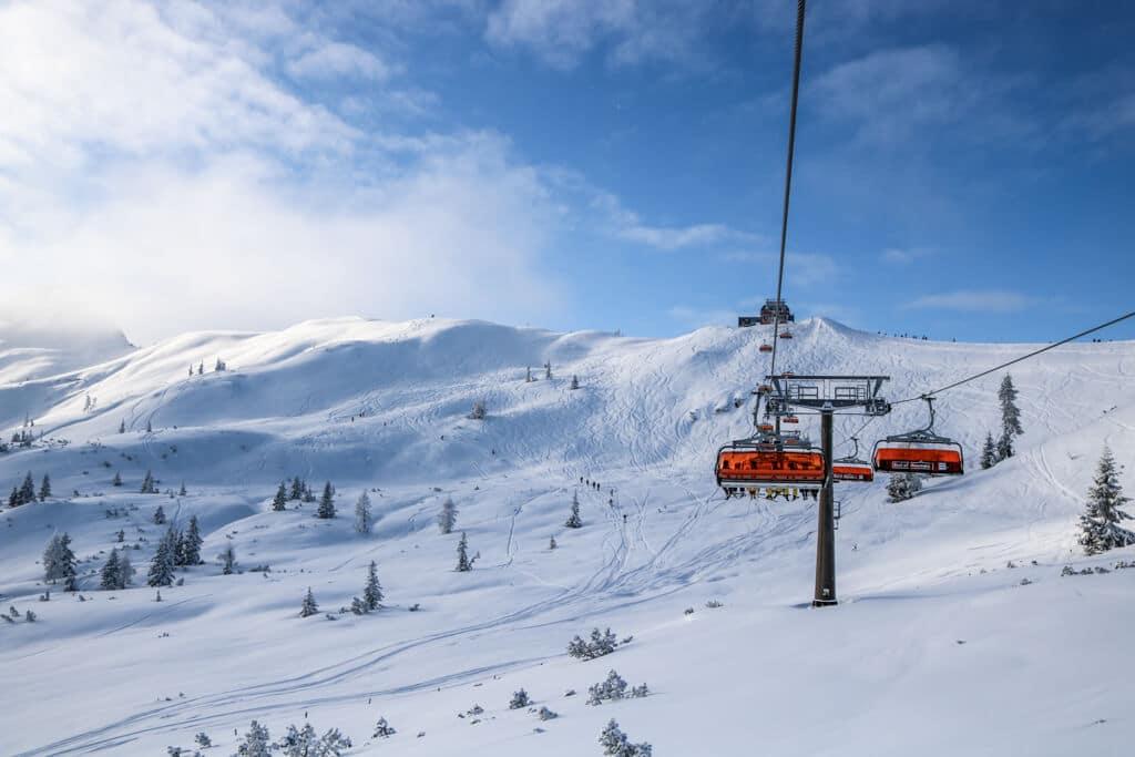 Ein Skilift mit Orangenen Hauben fährt durch die verschneiten Berge