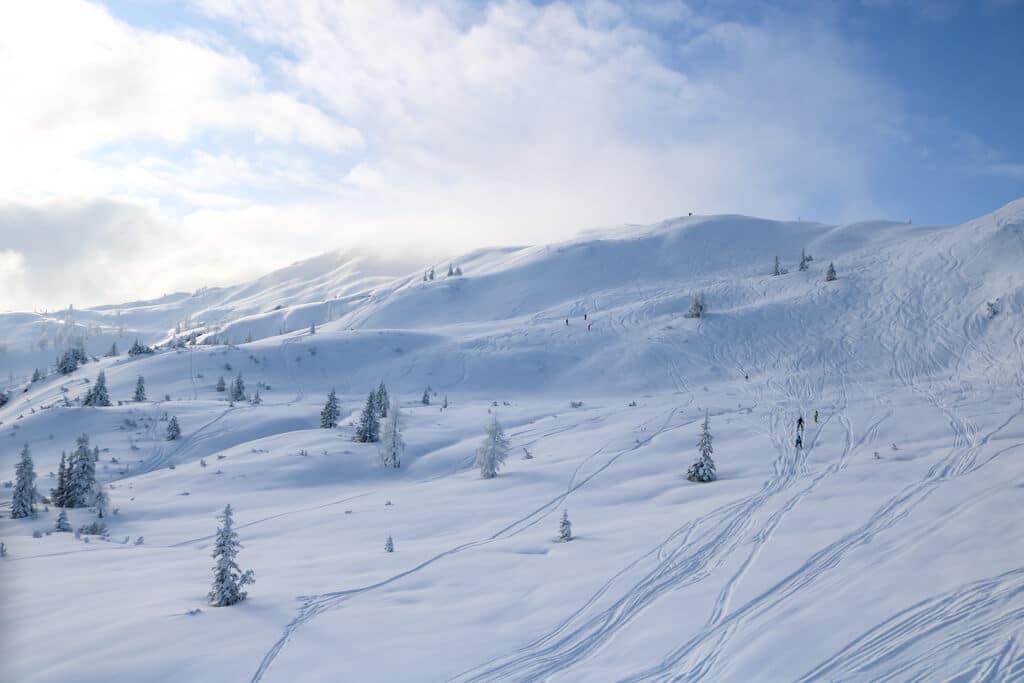 tief verschneite Berge mit vereinzelten Bäumen