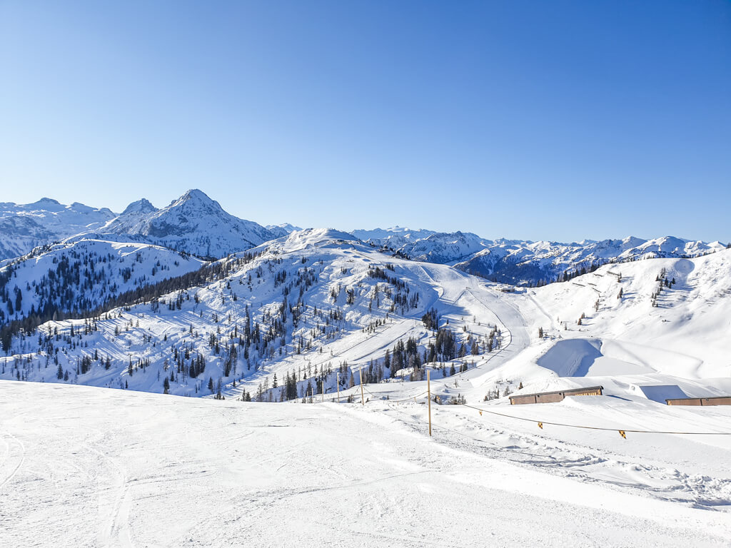 Ausblick über Skipisten bis hin zu schneebedeckten Berggipfeln