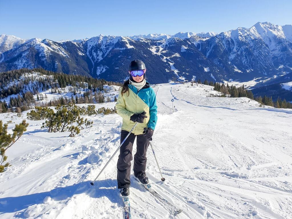Frau steht auf Skiern in den Bergen