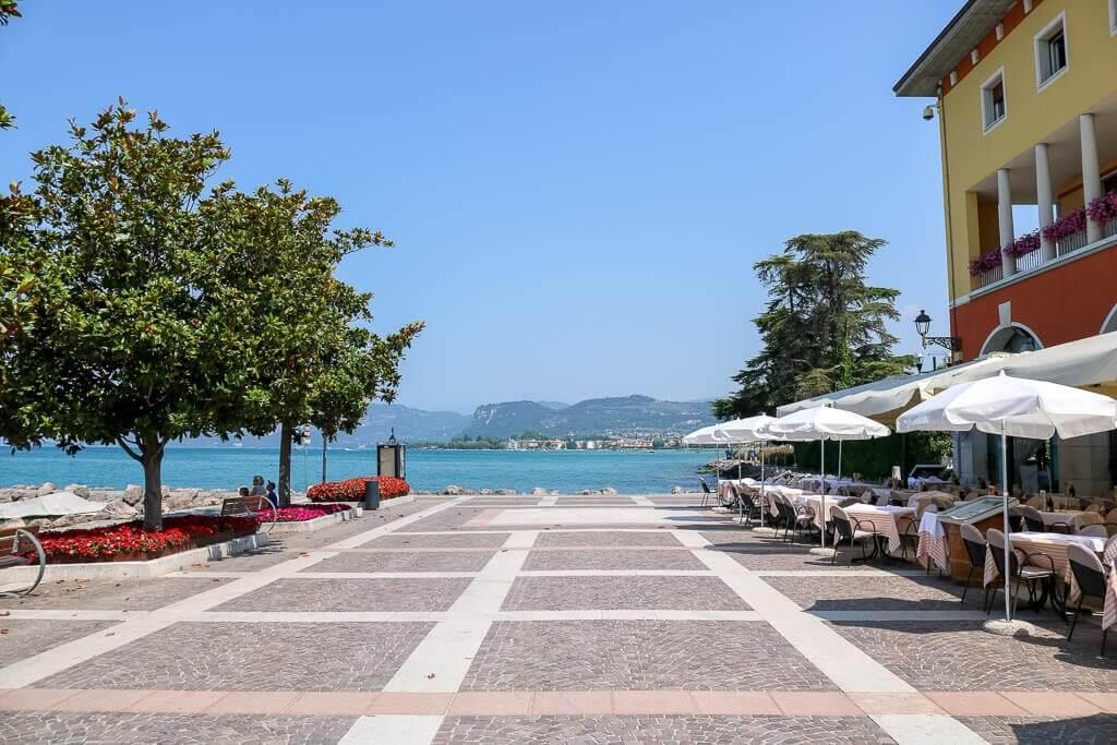 gepflasterter Platz mit Restaurants auf der rechten Seite, links ein Baum und im Hintergrund ein See