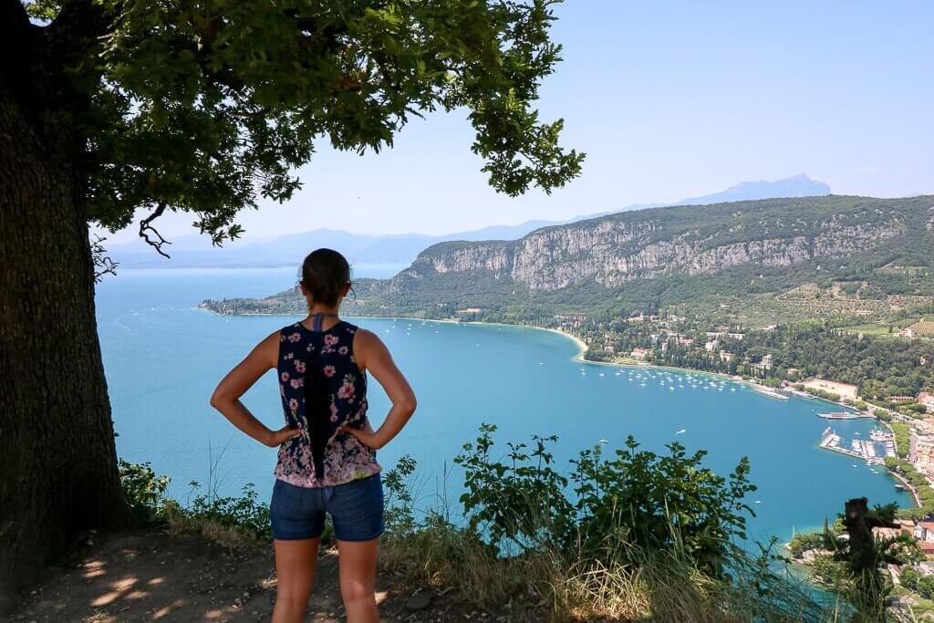 Frau steht auf einem Hügel mit Blick auf den Gardasee und die Küstenlinie