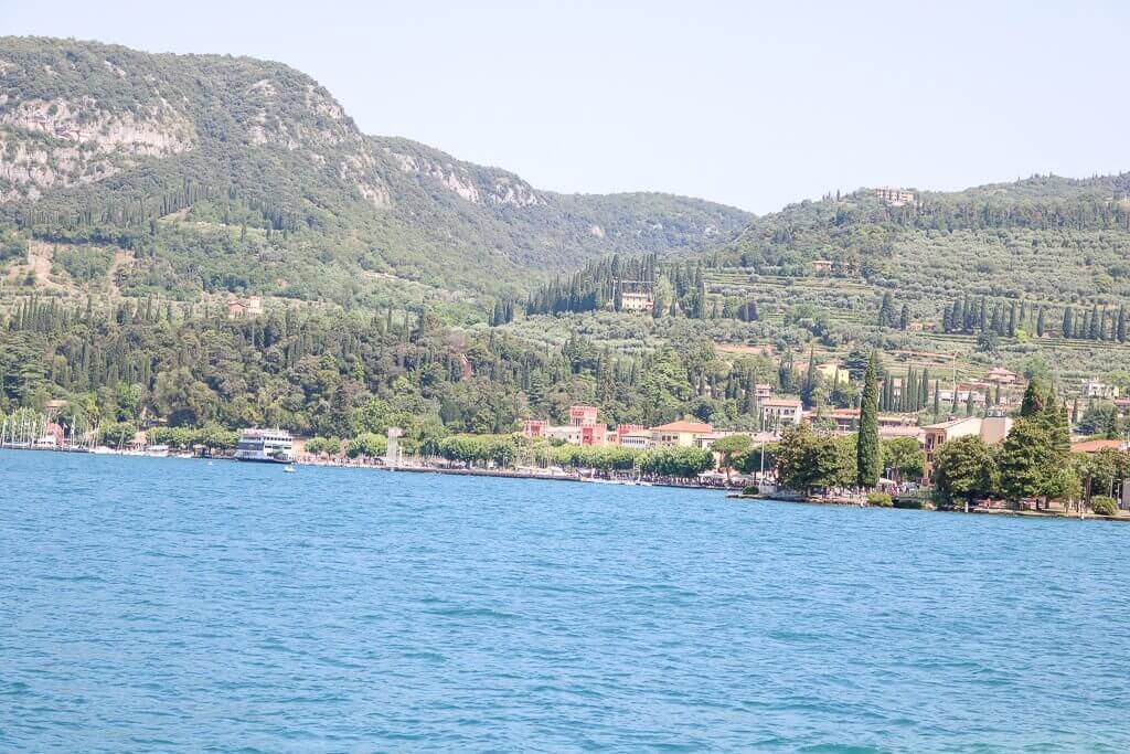 See mit Blick auf eine kleine Stadt, Wälder und Hügel im Hintergrund