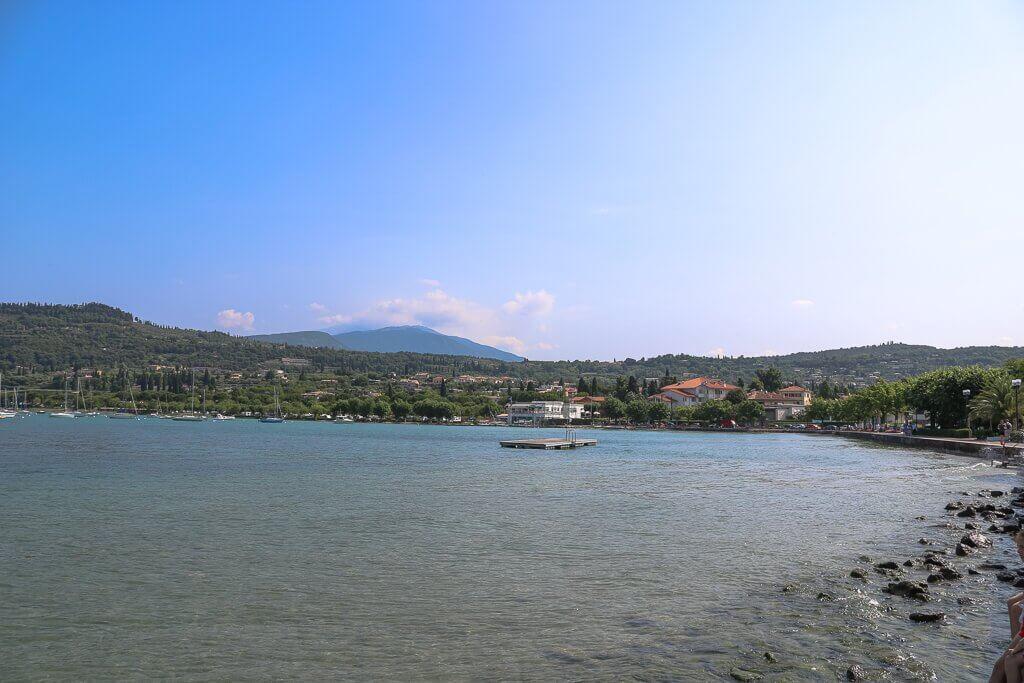 Gardasee mit Uferbereich im Vordergrund, in einer Linkskurve erheben sich Hügel und Land rund um den See