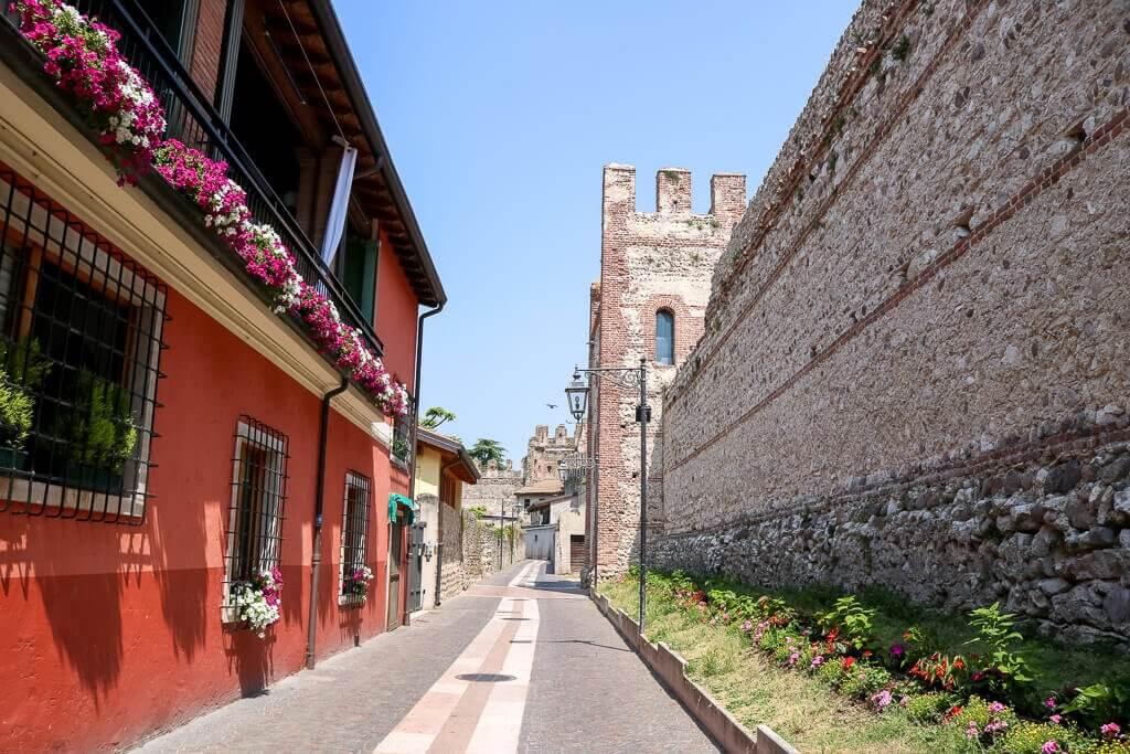 Stadtmauer auf der rechten Seite, links ein rot gestrichenes Haus mit Blumen