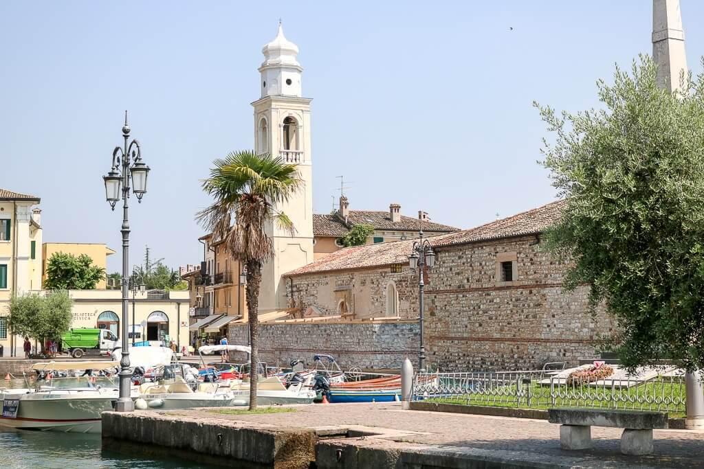 Turm umgeben von Steinhäusern und Palmen