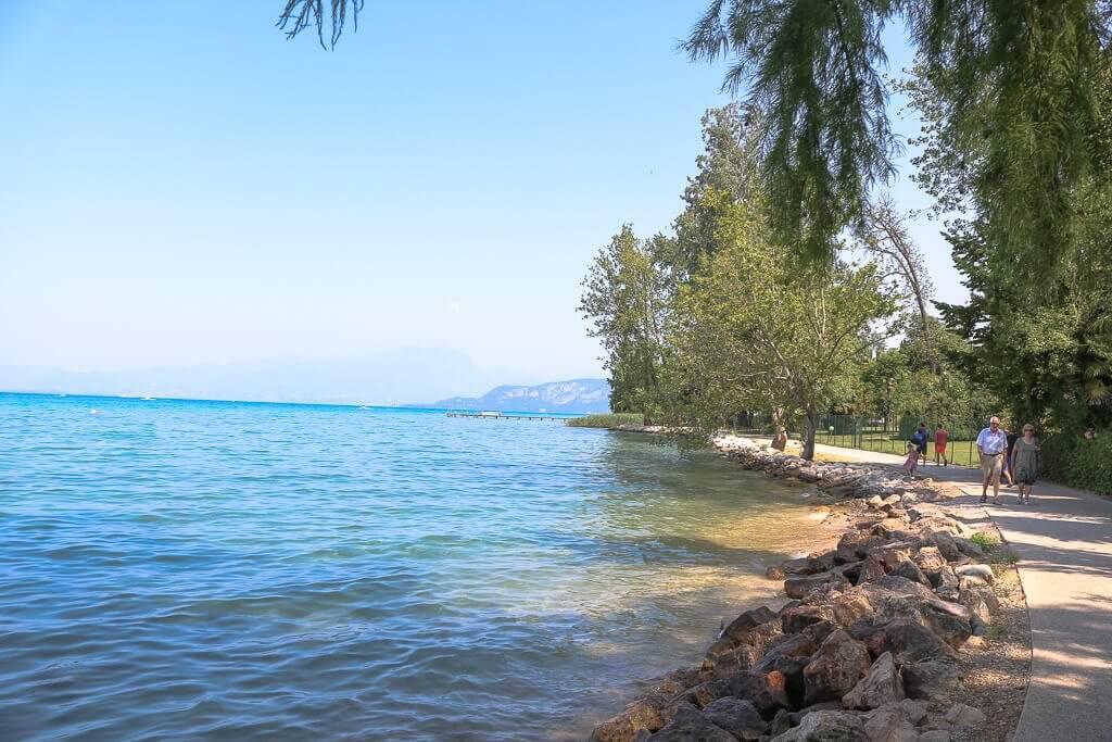 Uferpromenade mit Bäumen, daneben der Gardasee