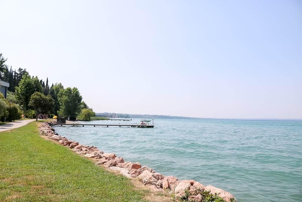 See auf der rechten Seite, links ein Weg mit Rasenstreifen