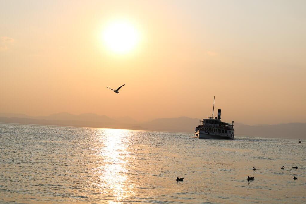 Sonnenuntergang über dem Wasser, eine Möwe fliegt und ein Boot im Hintergrund