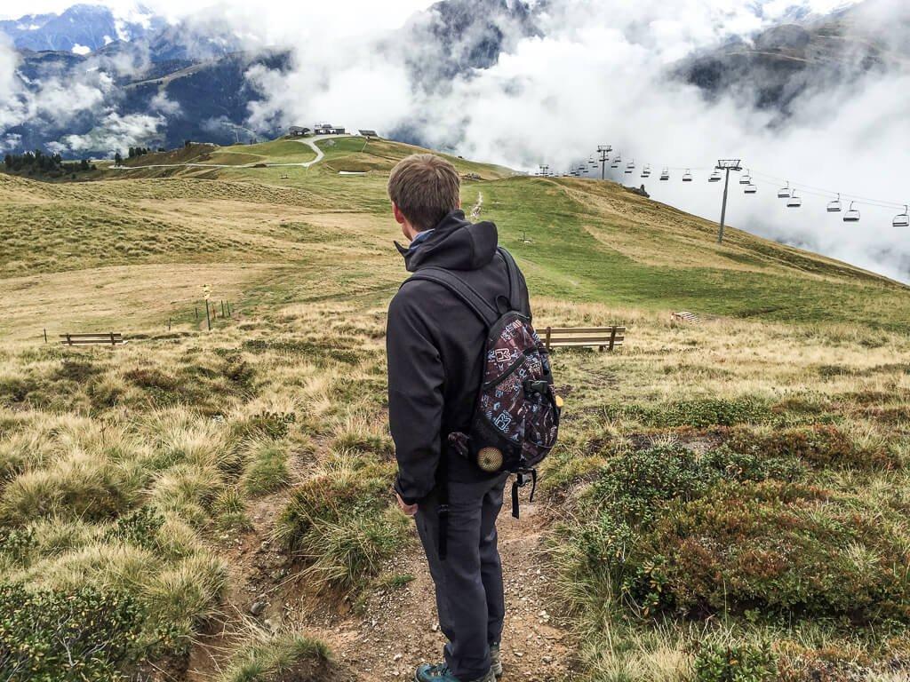 Mann steht auf einer Wiese in den Bergen - im Hintergrund ein Sessellift