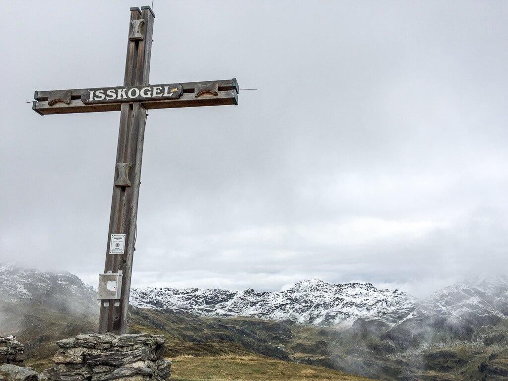 """Gipfelkreuz """"Isskogel"""" auf einem Felsen, dahinter erst grüne, dann schneebedeckte Berge"""