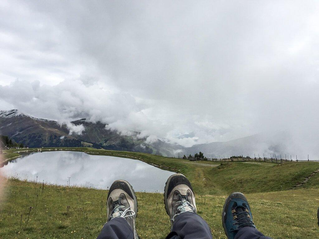 Beine mit Wanderschuhen - dahinter ein See und Berge