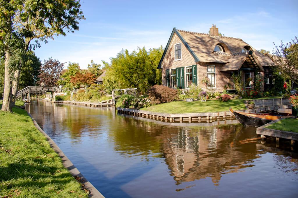 Reetdachhaus spiegelt sich im Wasser einer Gracht in Giethoorn