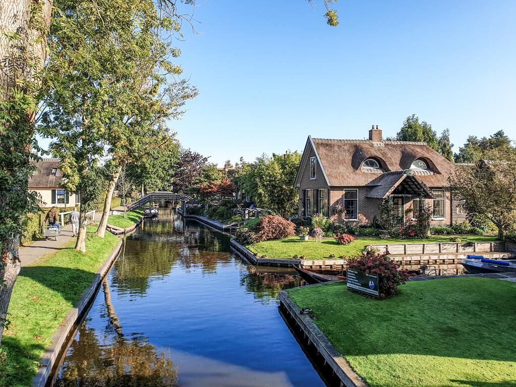 Giethoorn - Blick auf einige Häuser, die sich im Kanal spiegeln