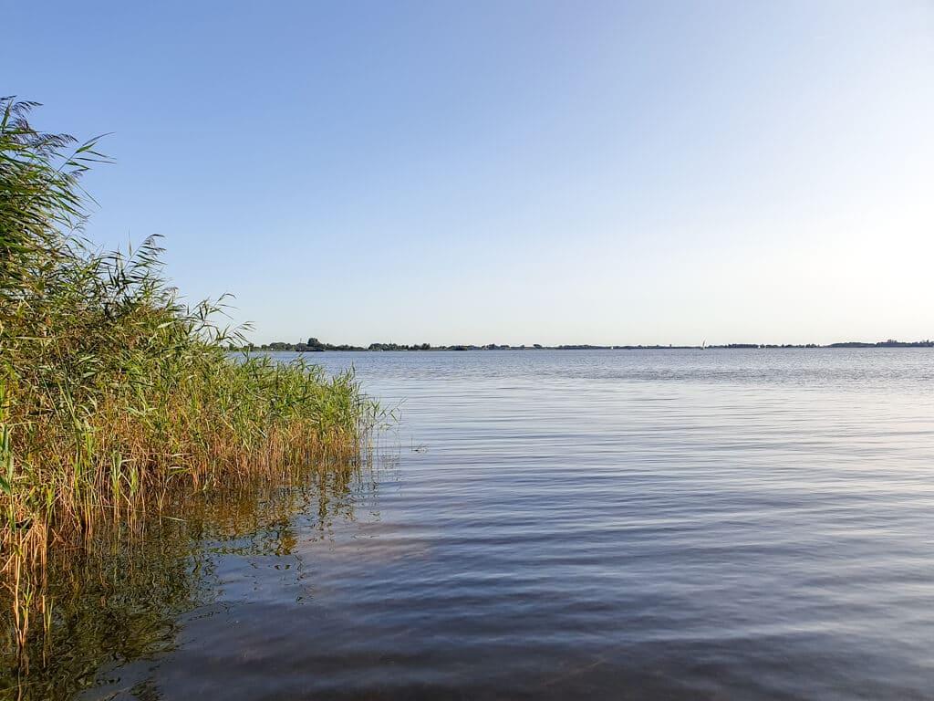 großer See mit Gras am linken Ufer