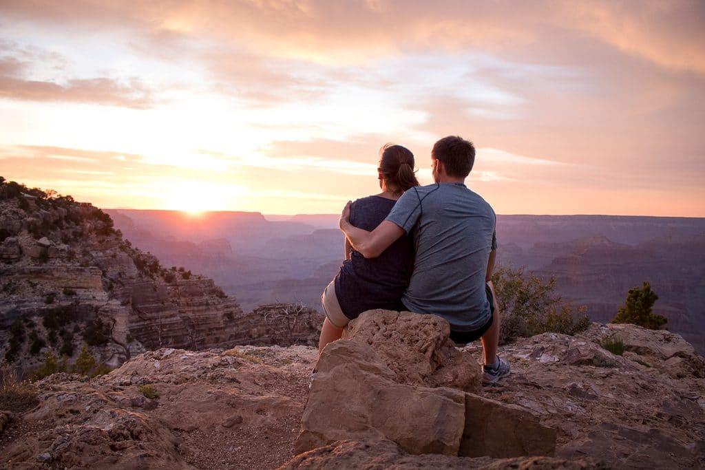Sonnenuntergang am Grand Canyon - Paar sitzt Arm in Arm und schaut in den Canyon