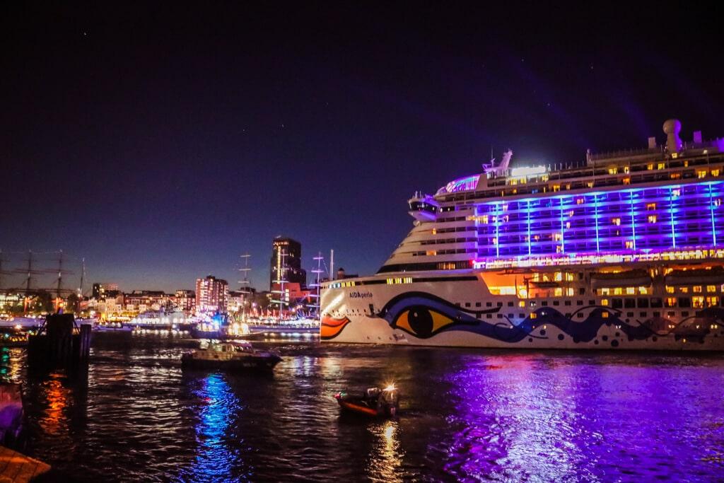 bunt beleuchtetes Kreuzfahrtschiff verlässt bei Nacht den Hafen in Hamburg