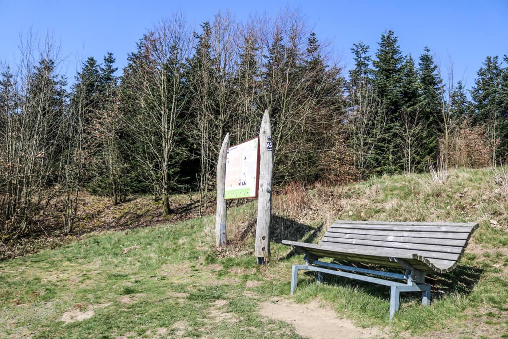 Bank und Wandertafel auf einer Wiese am Waldrand