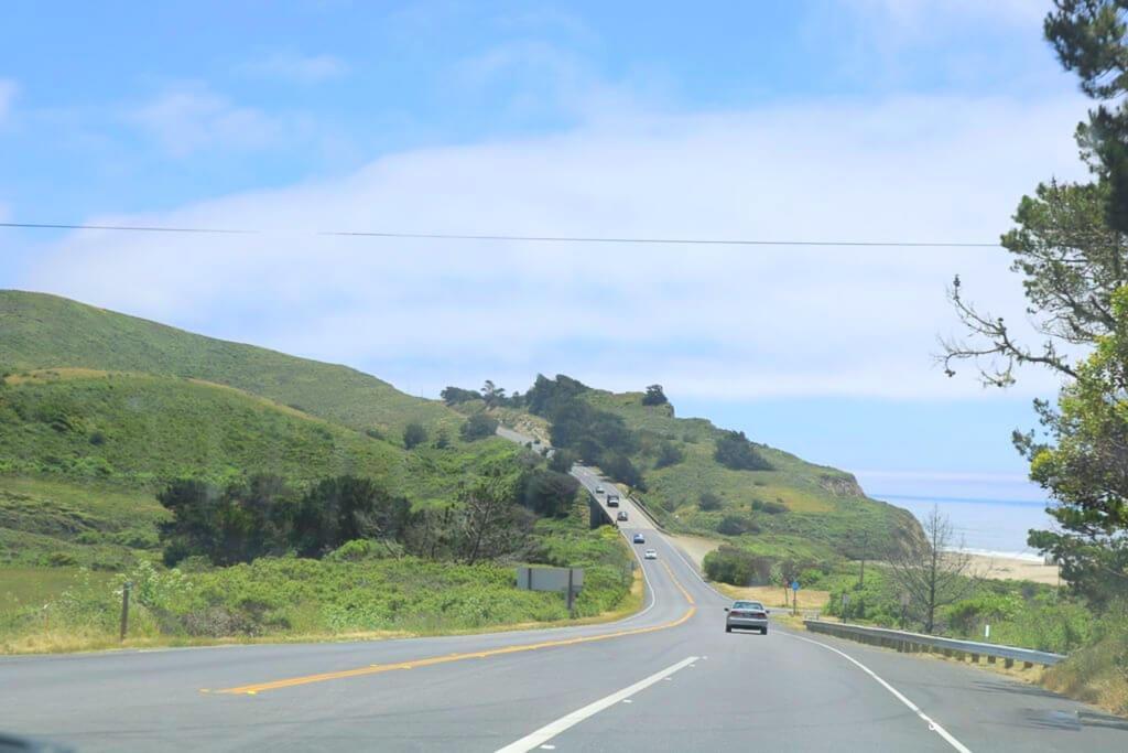 Straße führt einen Hügel hinab, umgben von grünen Wiesen. Am Horizont ist der Ozean zu erkennen