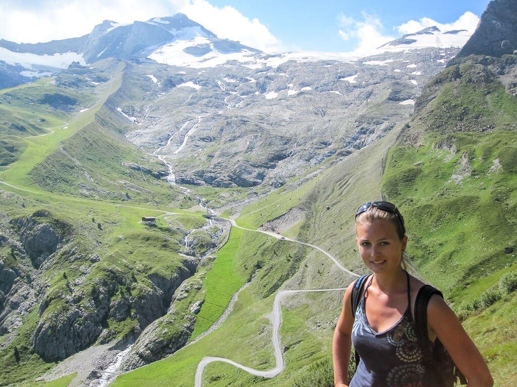 Frau im Vordergrund - restliches Bild sind Berge mit einem Weg und die hinteren Gipfel sind schneebedeckt