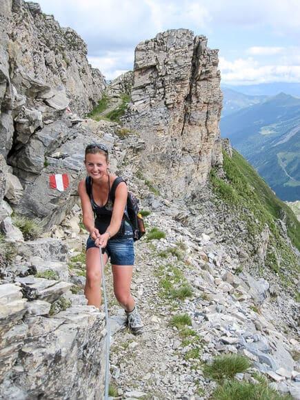 Frau steht auf schmalem Wanderweg und hält sich an einem Seil fest - rechts ein Abhang